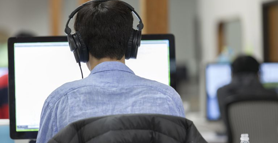 man with headset in front of computer